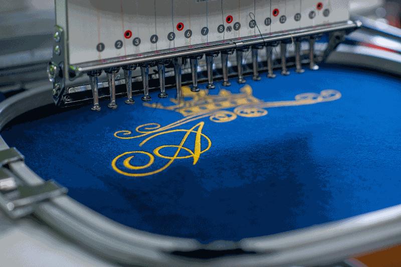 Stickmaschine, die goldenes Logo auf blauen Stoff stickt